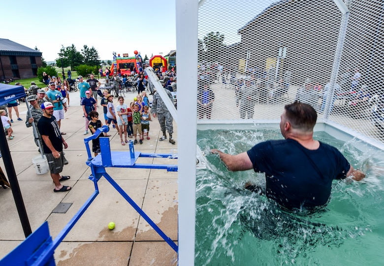Senior Master Sgt. Edward Mueller, 28th Logistics Readiness Squadron superintendent of fuels management, falls into a dunk tank during the annual base picnic outside the Dakota's Club on Ellsworth Air Force Base, S.D., June 22, 2018. The dunk tank event was part of the Air Force Ball Dunk-a-Leader fundraiser, which involved nominating base leadership to be dunked in a tank of water, and the money raised from the event will go toward the base's 2018 Air Force Ball in September. (U.S. Air Force photo by Senior Airman Randahl J. Jenson)