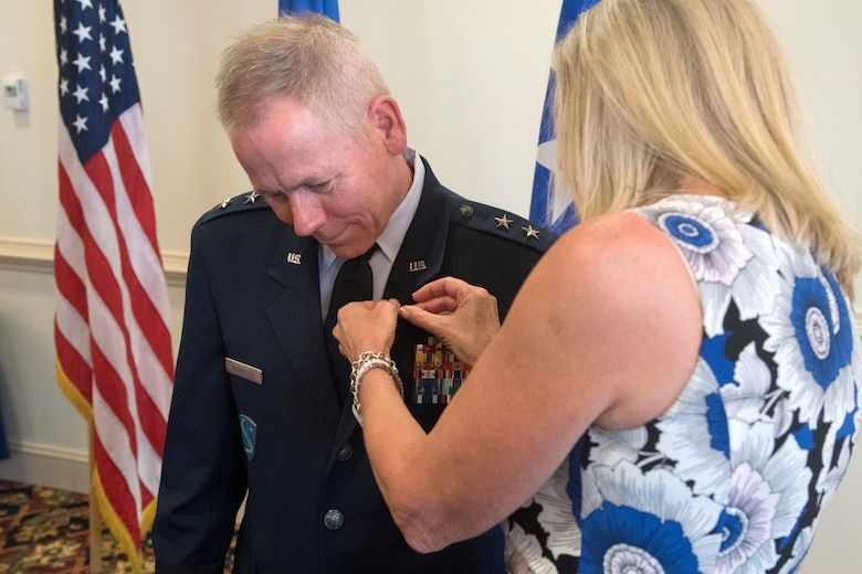 Kim McMullen attaches a retirement lapel pin on Maj. Gen. John K. McMullen, the deputy commander of Air Combat Command, during his retirement ceremony