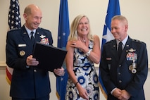 Gen. Mike Holmes, the commander of Air Combat Command, hands a spouse appreciation certificate to Kim McMullen during the retirement ceremony of her husband, Maj. Gen. John K. McMullen
