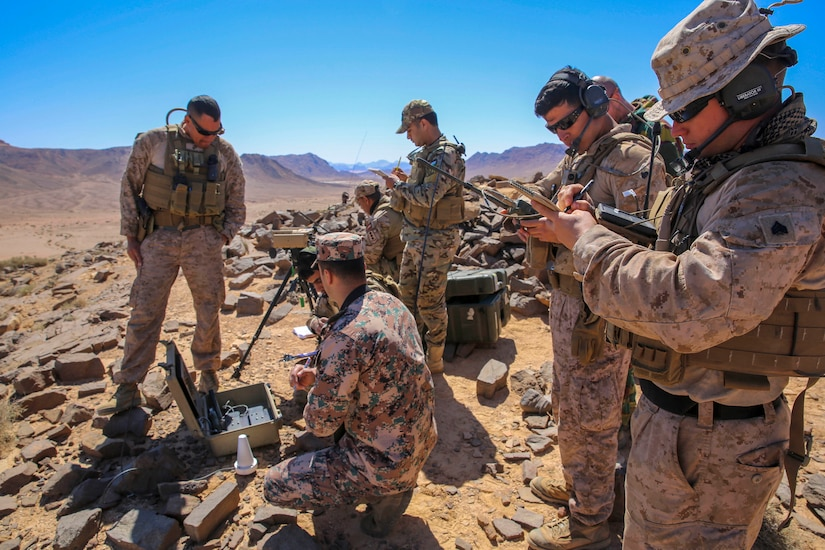 Service members set up and test communication and other equipment in a desert environment.