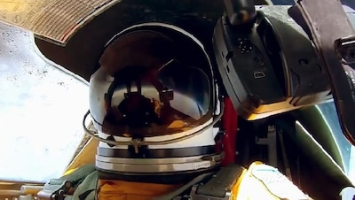 Pilot wearing helmet in cockpit