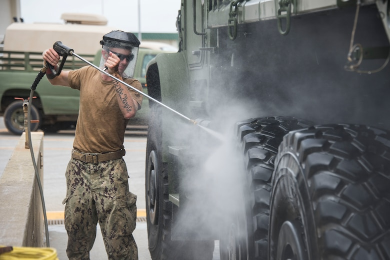Builder Constructionman Stephen Wetmore, from Deltona, Fl.,  assigned to Naval Mobile Construction Battalion (NMCB) 5, washes down a vehicle during a 48-hour Mount-Out Exercise (MOX) in Okinawa, Japan June 19. The MOX simulates one of the core capabilities of a construction battalion to deploy an air detachment, along with construction equipment, within 48-hours to any required location around the globe. NMCB 5 is forward deployed to execute construction, humanitarian and foreign assistance, and theater security cooperation support of United States Pacific Command.