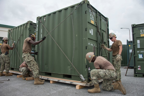 Seabees assigned to Naval Mobile Construction Battalion (NMCB) 5, chain a container to a pallet during a 48-hour Mount-Out Exercise (MOX) in Okinawa, Japan June 19. The MOX simulates one of the core capabilities of a construction battalion to deploy an air detachment, along with construction equipment, within 48-hours to any required location around the globe. NMCB 5 is forward deployed to execute construction, humanitarian and foreign assistance, and theater security cooperation support of United States Pacific Command.