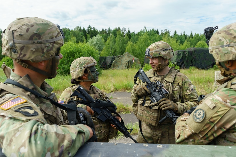 Army Spc. Lukas Natkevicius, second from right, a cavalry scout and Marijampole, Lithuania, native assigned to Headquarters and Headquarters Troop, 4th Squadron, 2nd Cavalry Regiment, smiles during a conversation with troops of his unit during Exercise Saber Strike 18 at a training area near Kazlu Ruda, Lithuania, June 7, 2018. Army photo by Sgt. Gregory T. Summers