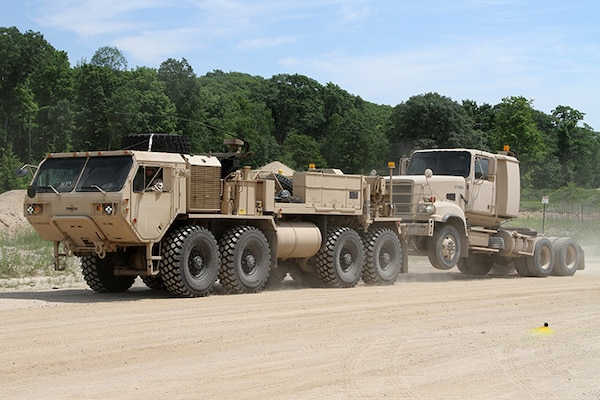 A Heavy Expanded Mobility Tactical Truck (HEMTT) A4 wrecker with the 211th Maintenance Company out of Newark, Ohio, tows a M915A5 truck tractor with the 1487th Transporation Company out of Piqua, Ohio, while completing tactical convoy operations training June 21, 2018, at the Camp Grayling Joint Maneuver Training Center in Grayling, Michigan.