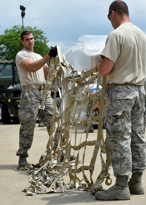 Staff Sgt. Nick Bailey and Tech Sgt. Richard Bauer prepare to place a cargo net on a pallet packed with supplies on the Youngstown Air Reserve Station flightline, June 3.