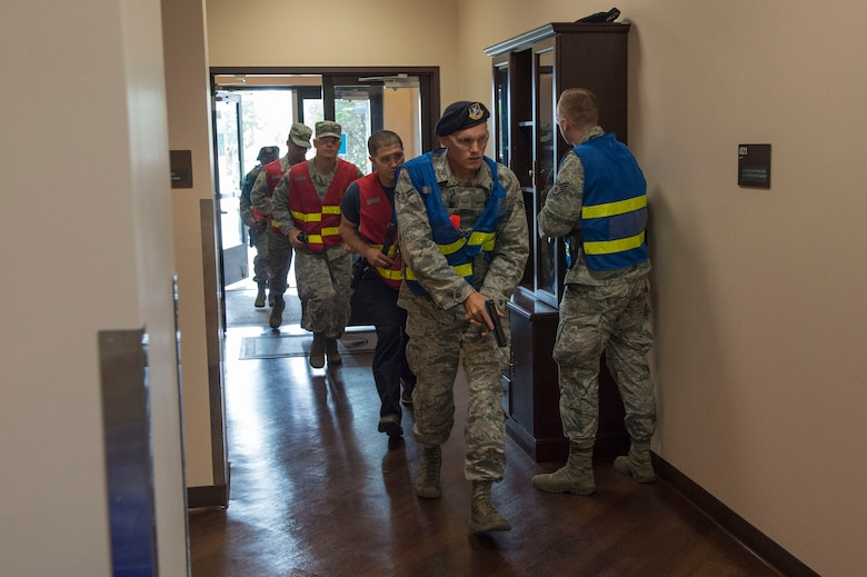 Members of the 97th Security Forces Squadron escort Altus Air Force Base fire fighters to aid the victims of an active shooter, during Advanced Law Enforcement Rapid Response Training, June 19, 2018, at Altus AFB, Okla.