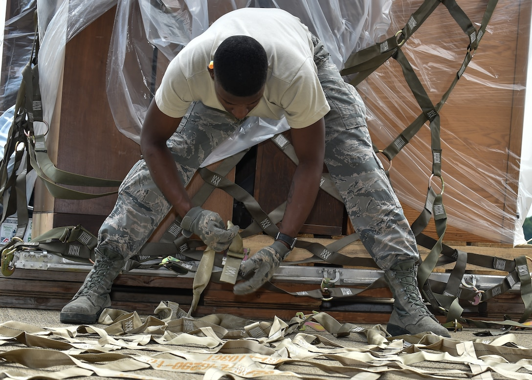 Airman 1st Class Kevin Mills, a 76th Aerial Port Squadron (APS) aerial transporter, lays out a cargo net  on the Youngstown Air Reserve station flightline, June 3.