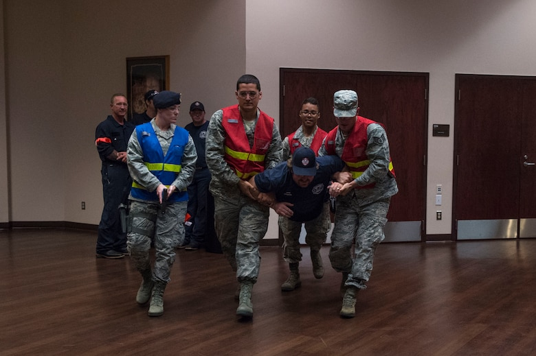 Altus Air Force Base fire fighters evacuate an injured victim, during Advanced Law Enforcement Rapid Response Training, June 19, 2018, at Altus AFB, Okla.