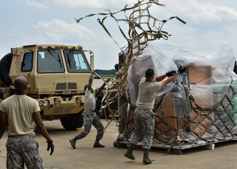 Staff Sgt. Donald Irby watches as Airman 1st Class Kevin Mills and Staff Sgt. Justin Knight, all 76th Aerial Port Squadron (APS) aerial transporters, toss a cargo net over a pallet of supplies on the Youngstown Air Reserve Station flightline, June 3.