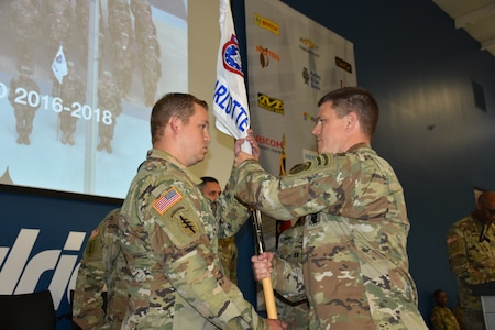 LTC Daniel Mitchell passes Charlotte Company Guidon to incoming Company Commander CPT Matthew King during the Change of Command Ceremony at Hendrick Motorsports Complex