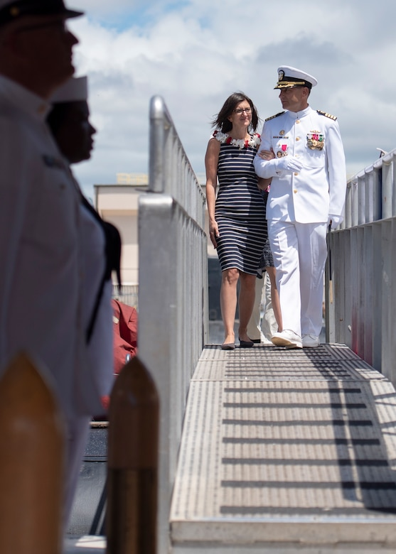 Capt. Robert A. Roncska (Ret.) and his family are piped ashore during the Submarine Squadron 7 change of command and retirement ceremony on the submarine piers in Joint Base Pearl Harbor-Hickam, June 22. (U.S. Navy photo by Mass Communication Specialist 2nd Class Michael H. Lee/Released)