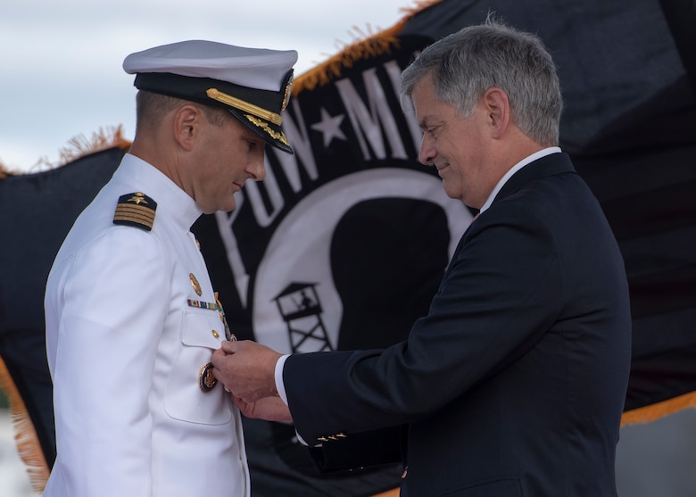 Capt. Dennis Murphy (Ret.) awards a Legion of Merit medal to Capt. Robert A. Roncska, commander, Submarine Squadron 7, during a change of command and retirement ceremony on the submarine piers in Joint Base Pearl Harbor-Hickam, June 22. (U.S. Navy photo by Mass Communication Specialist 2nd Class Michael H. Lee/Released)