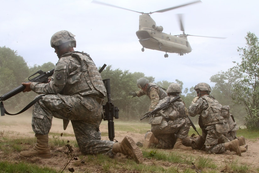 Soldiers prepare for a helicopter to land nearby.