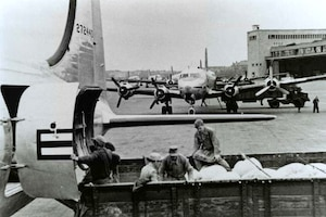 In a historic photo, people are unloading cargo from aircraft.