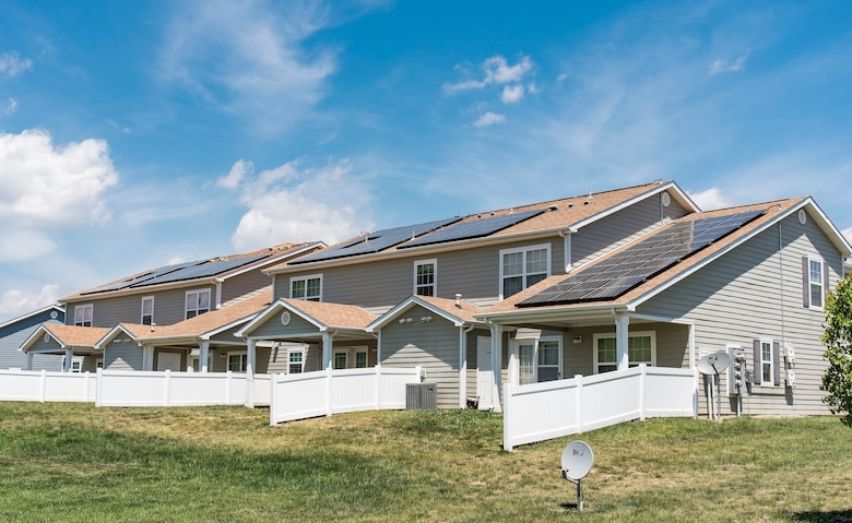 Photovoltaic (PV) panels installed on the back side of housing units in the Dover Family Housing community absorb sunlight to generate electricity May 11, 2018, at Dover Air Force Base, Del. Electricity generated by PV panels is transmitted to the electrical grid, not the individual housing units. Occupants will not see a reduction in their electricity bill. (U.S. Air Force photo by Roland Balik)