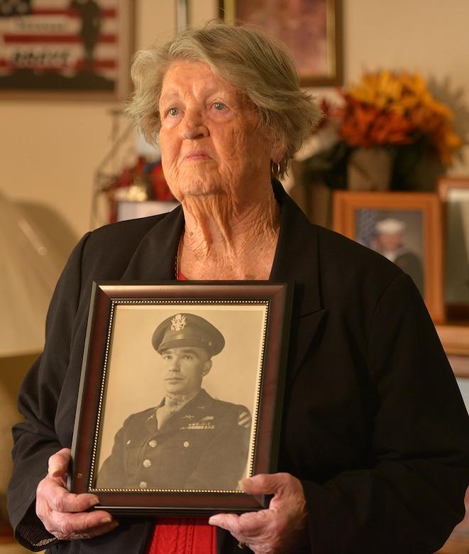 A widow holds a WWII-era photo of her husband.