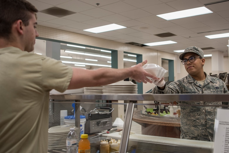 Airman 1st Class Gabriel Alvarez Indriago, 375th Force Support Squadron food service technician, serves a meal at the Nightingale Dining Facility, June 25th, 2018, at Scott Air Force Base, Illinois. The dining facility will be closed until the end of November to complete the renovations for the Food 2.0 initiative. (U.S. Air Force photo by Senior Airman Melissa Estevez)