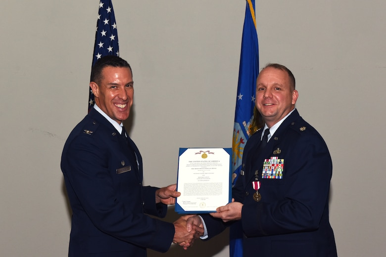 U.S. Air Force Col. Jason Beck, 17th Mission Support Group commander, presents a Meritorious Service Medal certificate to Lt. Col. John Travieso, 17th Contracting Squadron outgoing commander, during the 17th CONS Change of Command ceremony at the Event Center on Goodfellow Air Force Base, Texas, June 25, 2018. In fiscal year 17, Travieso's small team of 37 accounted for 64 percent of all Air Education Training Commands' savings. (U.S. Air Force photo by Airman 1st Class Zachary Chapman/Released)