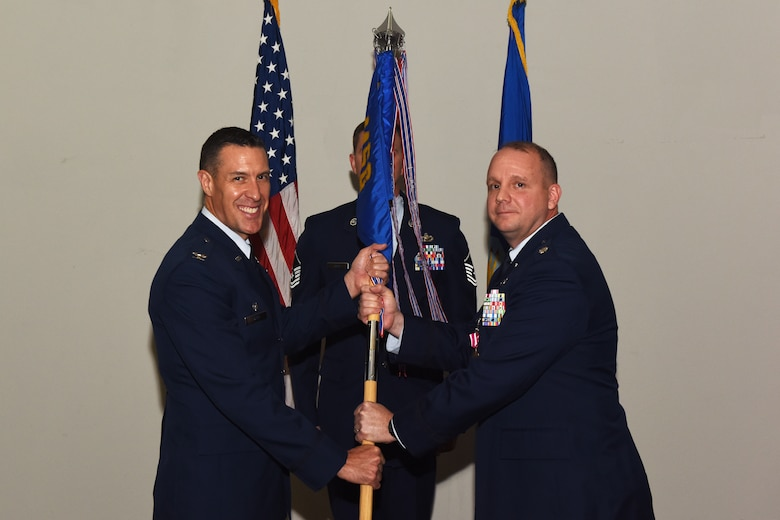 U.S. Air Force Col. Jason Beck, 17th Mission Support Group commander, accepts the 17th Contracting Squadron guideon from Lt. Col. John Travieso, 17th CONS outgoing commander, during the 17th CONS Change of Command ceremony at the Event Center on Goodfellow Air Force Base, Texas, June 25, 2018. The change of command ceremony is a time honored military tradition that signifies the orderly transfer of authority. (U.S. Air Force photo by Airman 1st Class Zachary Chapman/Released)