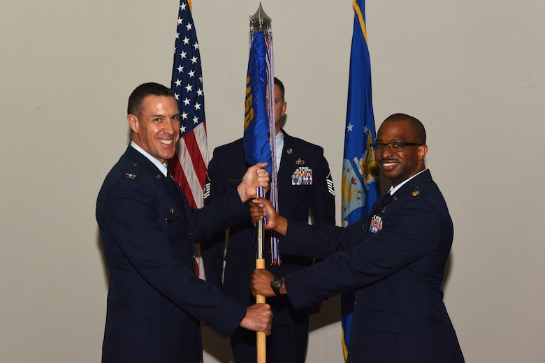 U.S. Air Force Col. Jason Beck, 17th Mission Support Group commander, passes the 17th Contracting Squadron guideon to Maj. Michael Quinn, 17th CONS incoming commander, at the 17th CONS Change of Command ceremony at the Event Center on Goodfellow Air Force Base, Texas, June 25, 2018. The guideon signifies the passing of command from one commander to the next. (U.S. Air Force photo by Airman 1st Class Zachary Chapman/Released)