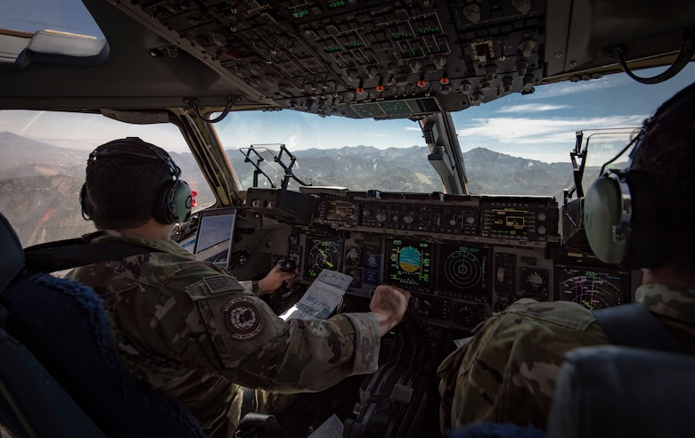 Maj. David Rodriguez, 732nd Airlift Squadron Instructor Pilot, and Capt. Ali Chinisaz, 6th Airlift Squadron instructor pilot, prepare to perform low-altitude, evasive maneuvers in a C-17 Globemaster III cargo aircraft over the Nevada Test and Training Range, June 9, 2018. The C-17 is capable of performing rapid strategic delivery of troops and all types of cargo. (U.S. Air Force photo by Airman 1st Class Andrew D. Sarver)