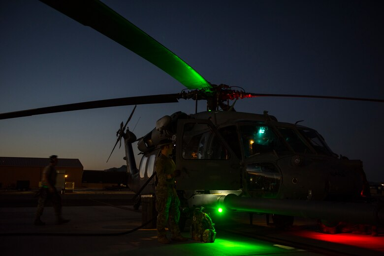 A crew prepares an HH-60G Pave Hawk helicopter prior to a large-scale U.S. Air Force Weapons School Integration Phase training exercise June 11, 2018 at Nellis Air Force Base, Nev. The USAFWS trains tactical experts and leaders to control and exploit air, space and cyberspace assets on behalf of the joint force. (U.S. Air Force photo by Staff Sgt. Joshua Kleinholz)