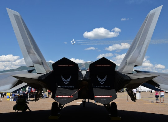 The U. S. Air Force Thunderbirds demonstration squadron in the diamond formation passes between the vertical stabilizers of an F-22 Raptor during the Warriors over the Wasatch Air and Space Show  June 23, 2018, at Hill Air Force Base, Utah, 2018. The Raptor was part of the static displays put out  by the Ogden Air Logistics Complex for air show visitors to view and photograph.  (U.S. Air Force photo by Alex R. Lloyd)