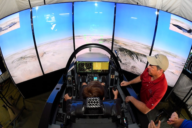 Air show visitors experience a Lockheed Martin F-35 simulator June 24, 2018, at Hill Air Force Base, Utah. Some of the largest aerospace companies in the world brought interative exhibits and displays to the Warriors Over the Wasatch Air and Space Show. (U.S. Air Force photo by Todd Cromar)