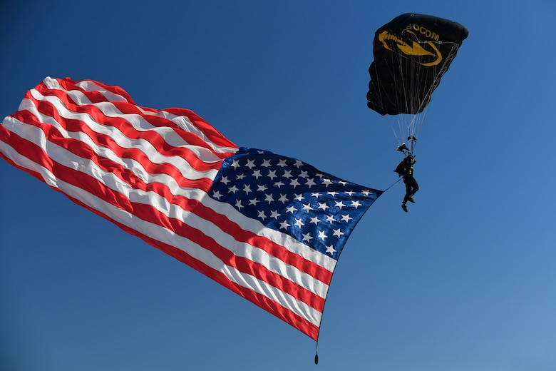 A U.S. Special Operations Command Para-Commando parachute demonstration member parahutes in to the Warriors Over the Wasatch Air and Space Show carrying the American flag June 24, 2018, at Hill Air Force Base, Utah. (U.S. Air Force photo by Todd Cromar)