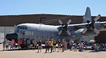 Airshow visitors use the large shadow cast by a U. S. Navy C-130H Hercules to keep cool during the Warriors over the Wasatch Air and Space Show June 23, 2018, at Hill Air Force Base, Utah. (U.S. Air Force photo by Alex R. Lloyd)