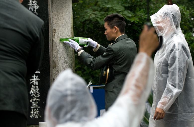 A Japanese military member pours sake onto the Japanese memorial