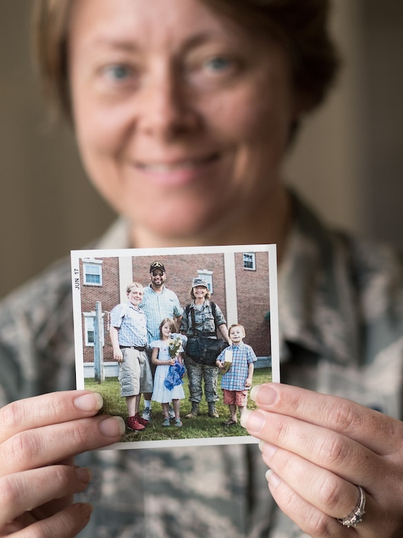Airman 1st Class Crystal Jenkins, a photojournalist assigned to the 673d Air Base Wing Public Affairs unit, holds a photo of her and her family after she graduated from Defense Information School at Fort Meade, Md., in 2017. Jenkins was inspired to join the U.S. Air Force during the 2016 Arctic Thunder Open House at Joint Base Elmendorf-Richardson, Alaska. After enlisting in 2016 she was given the opportunity to return to the base she was recruited from.