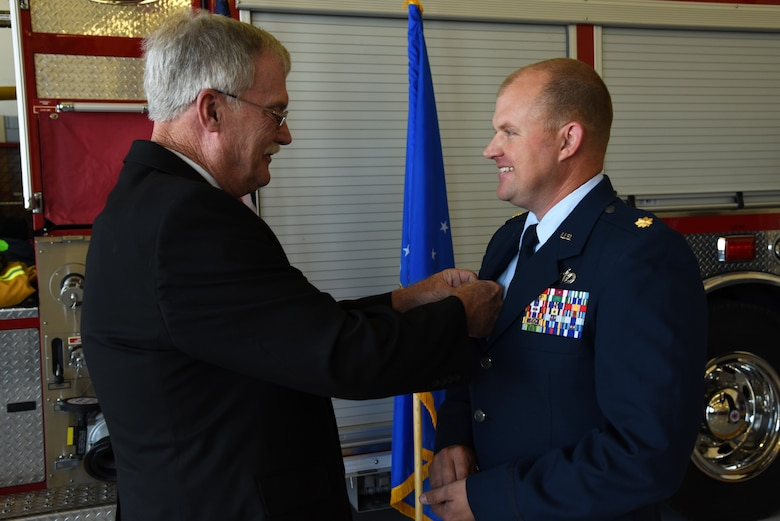U.S. Air Force Maj. Nicholas Anderson, 17th Civil Engineer Squadron commander, receives his commander's pin from his father during the 17th CES Assumption of Command at the fire department on Goodfellow Air Force Base, Texas, June 22, 2018. The pin signifies that individual holds the position of commander of a squadron, group, wing or major command. (U.S. Air Force photo by Staff Sgt. Joshua Edwards/Released)