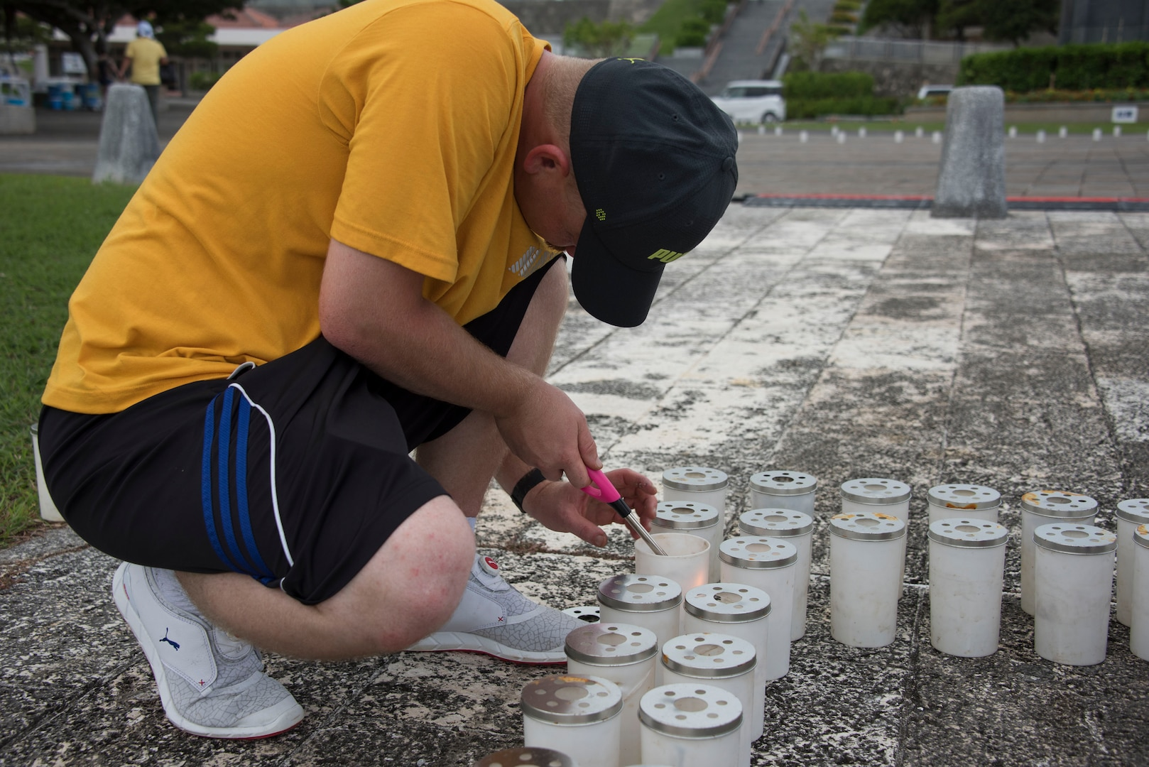 Aviation Electrician's Mate Chief Greg Brown, from Wilmington, N.C., assigned to Patrol Squadron (VP) 4, lights a candle at Okinawa Peace Memorial Park during the Lamplight of Peace event. More than 30 U.S. Navy volunteers carefully placed thousands of ceremonial candles at the park in Itoman City, June 22, to honor the more than 250,000 Japanese and American lives lost during the Battle of Okinawa, the third deadliest battle ever fought by U.S. service members.