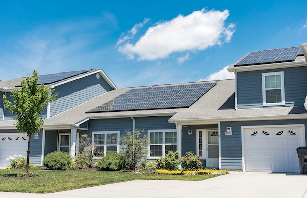 Photovoltaic (PV) panels installed on the front side of two houses in the Dover Family Housing community absorb sunlight to generate electricity May 11, 2018, at Dover Air Force Base, Del. Electricity generated by PV panels is transmitted to the electrical grid, not the individual house or houses. Occupants will not see a reduction in their electricity bill. (U.S. Air Force photo by Roland Balik)