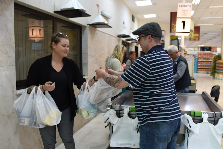 U.S. Air Force Master Sgt. Travis Lacy, 39th Force Support Squadron superintendent of manpower, organization and continuous process improvement, hands groceries to a customer at the Commissary at Incirlik Air Base, Turkey, June 19, 2018.