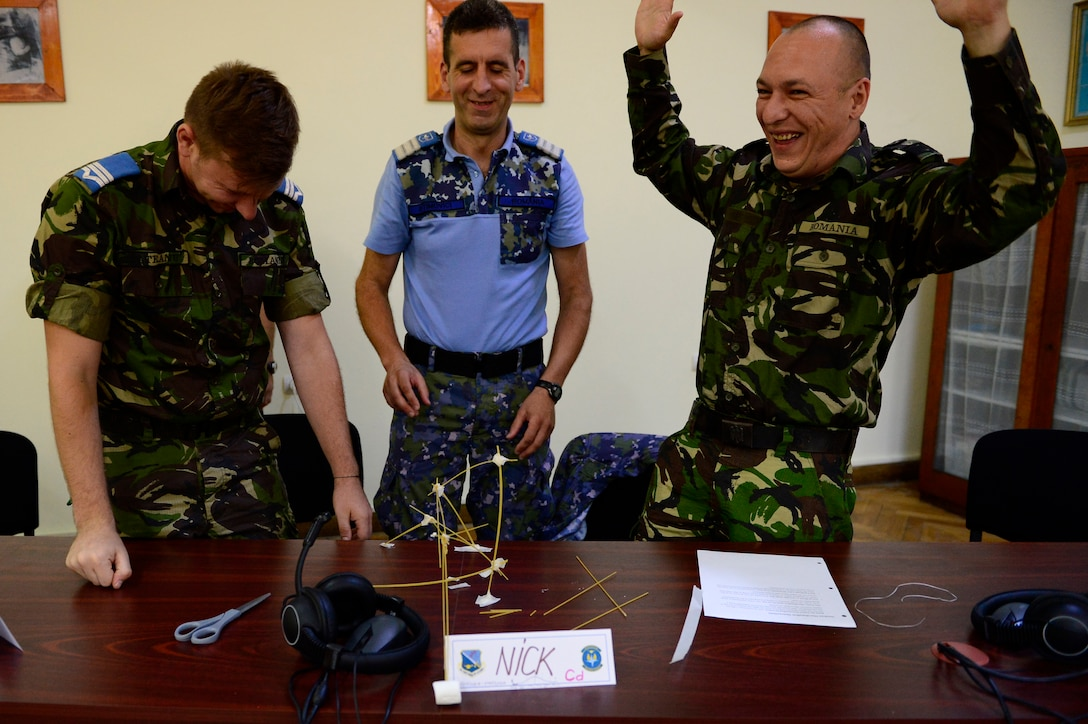 Three Romanian Air Force students react as their structure falls over during a strategic thinking exercise during the first-ever senior noncom missed officer mobile education course June 8 to 22, 2018, at Boboc Air Base, in Buzău, Romania. The SNCOA mobile training team partnered with the Inter-European Air Forces Academy to provide a two-week course, condensed from the full five-week course held at Maxwell Air Force Base- Gunter Annex, Alabama. (U.S. Air Force photo by Tech. Sgt. Staci Kasischke)