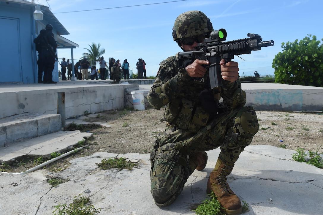 A Mexican Marine takes a knee while aiming a rifle.