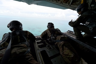 Members of the Rhode Island National Guard look out from the back of an airplane