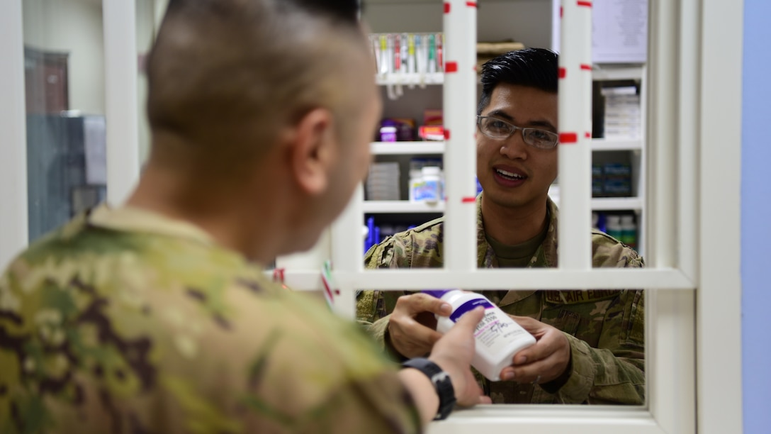 Tech. Sgt. Julian Tayag, 386 EMDG pharmacy non-commissioned officer-in-charge, provides medication to a coworker June 22, 2018, at an undisclosed location in Southwest Asia. In early May 2018, Tayag was selected to attend the Interservice Physician Assistant Program. (U.S. Air Force photo by Staff Sgt. Christopher Stoltz)