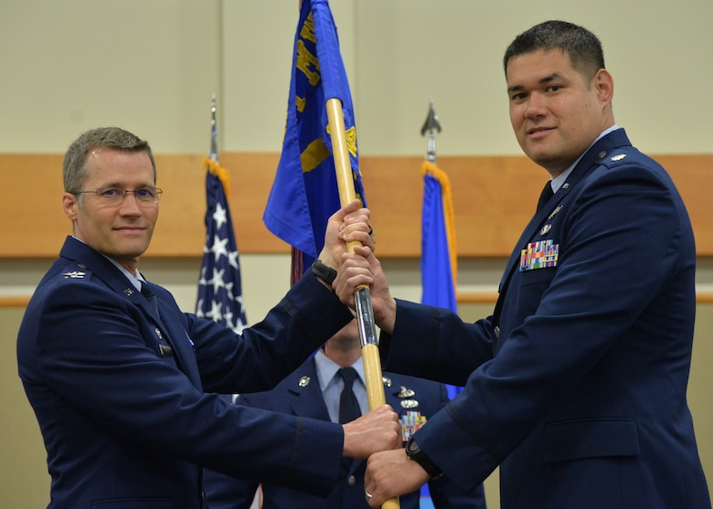 Lt. Col. Alan Haedge, right, accepts command of the 341st Communications Squadron from Col. Marcus Glenn, 341st Mission Support Group commander during a change of command ceremony June 25, 2018, at the Grizzly Bend on Malmstrom AFB, Mont.