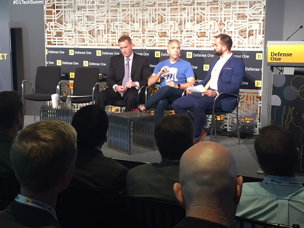 Three men speak as a panel at a technology summit.