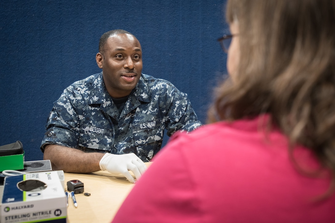 U.S. Navy HM2 Frederick Bessent, a medical support sailor from Naval Operation Support Center in Pittsburgh, takes the medical history of a local resident at a no-cost health-care clinic at Lee County High School in Beattyville, Ky., June 15, 2018. The clinic is one of four that was staffed by military health-care professionals in Eastern Kentucky from June 15 to June 24 as part of an Innovative Readiness Training mission called Operation Bobcat. The mission provided military forces with crucial expeditionary training while offering no-cost medical, dental and optometry care to area residents. (U.S. Air National Guard photo by Lt. Col. Dale Greer)