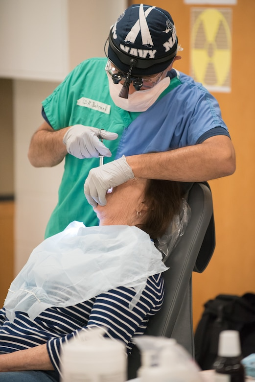 U.S. Navy Cmdr. Hayder Bahrani, a dentist from Expeditionary Medical Facility Great Lakes in Illinois, prepares a patient for a tooth extraction at a health-care clinic being operated by the Air Guard and U.S. Navy Reserve at Breathitt County High School in Jackson, Ky., June 20, 2018. The Jackson clinic is one of four that comprised Operation Bobcat, a 10-day mission to provide military medical troops with crucial training in field operations and logistics while offering no-cost health care to the residents of Eastern Kentucky. The clinics, which operated from June 15-24, offered non-emergent medical care; sports physicals; dental cleanings, fillings and extractions; eye exams and no-cost prescription eye glasses. (U.S. Air National Guard photo by Lt. Col. Dale Greer)