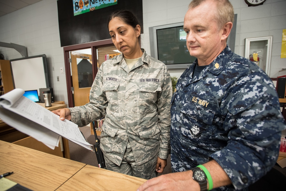 U.S. Air Force Master Sgt. Nikki Nazworth (left), from the Kentucky Air National Guard's 123rd Airlift Wing, discusses patient care with U.S. Navy Lt. Cmdr. Frank McKeown, a registered nurse from Expeditionary Medical Facility Bethesda in Maryland, at a health-care clinic being run by the Air Guard and U.S. Navy Reserve at Owsley County High School in Booneville, Ky., June 20, 2018. The clinic is one of four that comprised Operation Bobcat, a 10-day mission to provide military medical troops with crucial training in field operations and logistics while offering no-cost health care to the residents of Eastern Kentucky. The clinics, which operated from June 15-24, offered non-emergent medical care; sports physicals; dental cleanings, fillings and extractions; eye exams and no-cost prescription eye glasses. (U.S. Air National Guard photo by Lt. Col. Dale Greer)