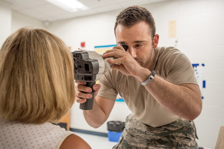 U.S. Air Force Senior Airman Dane Mendelsohn, a medic from the Kentucky Air National Guard's 123rd Airlift Wing, screens an optometry patient at a health-care clinic being operated by the Air Guard and U.S. Navy Reserve at Breathitt County High School in Jackson, Ky., June 20, 2018. The Jackson clinic is one of four that comprised Operation Bobcat, a 10-day mission to provide military medical troops with crucial training in field operations and logistics while offering no-cost health care to the residents of Eastern Kentucky. The clinics, which operated from June 15-24, offered non-emergent medical care; sports physicals; dental cleanings, fillings and extractions; eye exams and no-cost prescription eye glasses. (U.S. Air National Guard photo by Lt. Col. Dale Greer)
