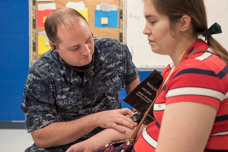 U.S. Navy HM2 Eric Bales, a corpsman from Expeditionary Medical Facility Great Lakes in Illinois, takes a patient's blood pressure at a health-care clinic being operated by the Air National Guard and U.S. Navy Reserve at Breathitt County High School in Jackson, Ky., June 20, 2018. The Jackson clinic is one of four that comprised Operation Bobcat, a 10-day mission to provide military medical troops with crucial training in field operations and logistics while offering no-cost health care to the residents of Eastern Kentucky. The clinics, which operated from June 15-24, offered non-emergent medical care; sports physicals; dental cleanings, fillings and extractions; eye exams and no-cost prescription eye glasses. (U.S. Air National Guard photo by Lt. Col. Dale Greer)