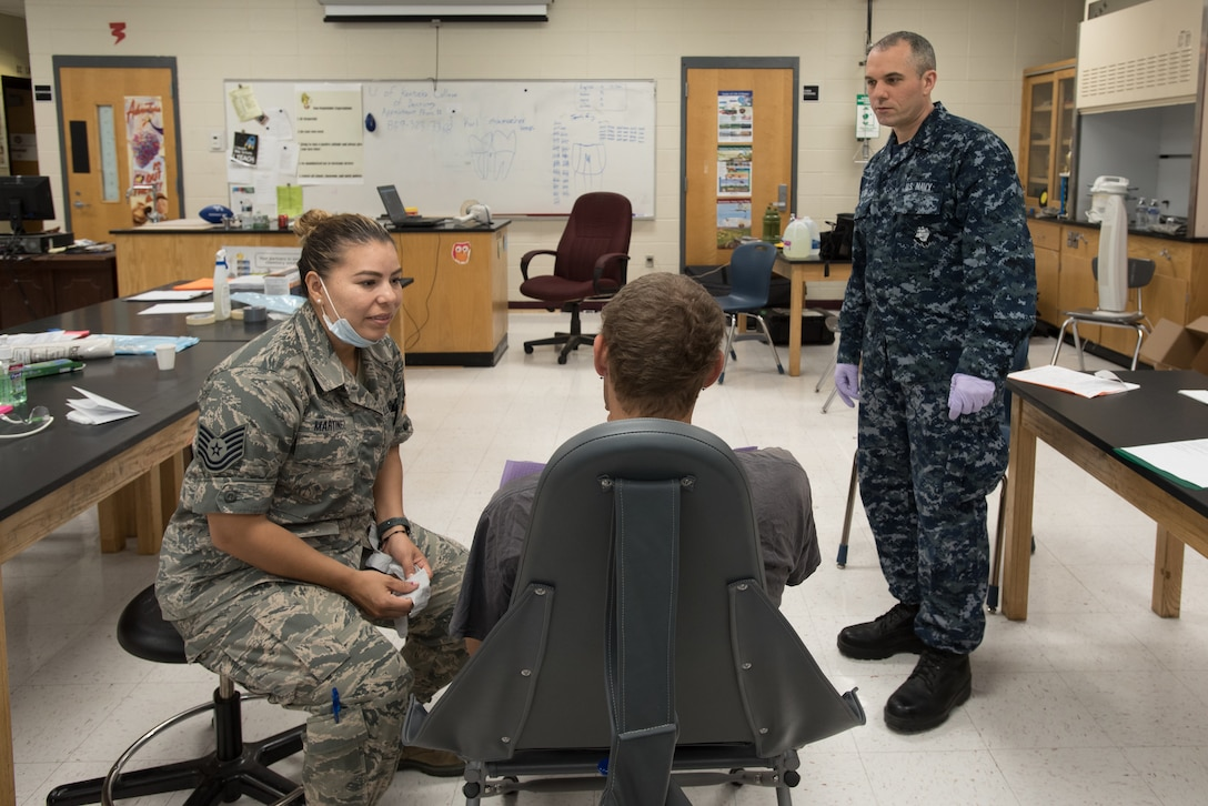 U.S. Air Force Tech. Sgt. Jessica Martinez (left), a dental technician from the Iowa Air National Guard's 185th Refueling Wing, and U.S. Navy HM3 Jason Dow, a corpsman from Expeditionary Medical Facility Bethesda in Maryland, talk with a dental patient at a health-care clinic at Owsley County High School in Booneville, Ky., June 24, 2018. The clinic is one of four that comprised Operation Bobcat, a 10-day mission to provide military medical troops with crucial training in field operations and logistics while offering no-cost health care to the residents of Eastern Kentucky. The clinics, which operated from June 15-24, offered non-emergent medical care; sports physicals; dental cleanings, fillings and extractions; eye exams and no-cost prescription eye glasses. (U.S. Air National Guard photo by Lt. Col. Dale Greer)