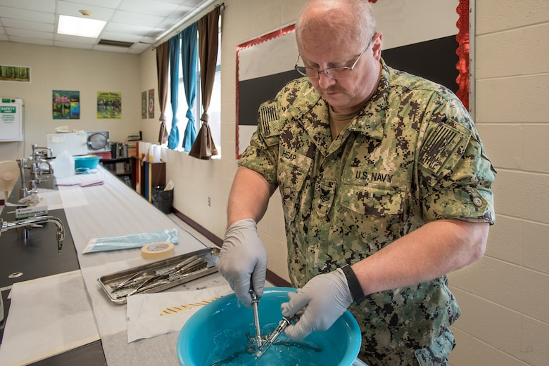 U.S. Navy HM1 Billy Joe Heap, a corpsman from Expeditionary Medical Facility Dallas, sterilizes dental instruments at a health-care clinic at Owsley County High School in Booneville, Ky., June 24, 2018. The clinic is one of four that comprised Operation Bobcat, a 10-day mission to provide military medical troops with crucial training in field operations and logistics while offering no-cost health care to the residents of Eastern Kentucky. The clinics, which operated from June 15-24, offered non-emergent medical care; sports physicals; dental cleanings, fillings and extractions; eye exams and no-cost prescription eye glasses. (U.S. Air National Guard photo by Lt. Col. Dale Greer)